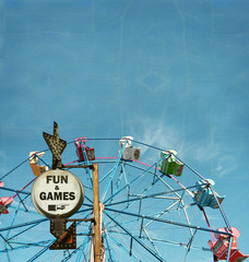 aged and worn vintage photo of ferris wheel with fun and games sign