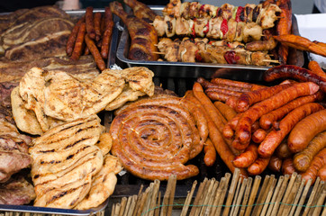 Delicious grilled meat with vegetable on a barbecue. Closeup of fried meat and sausages on a grill.