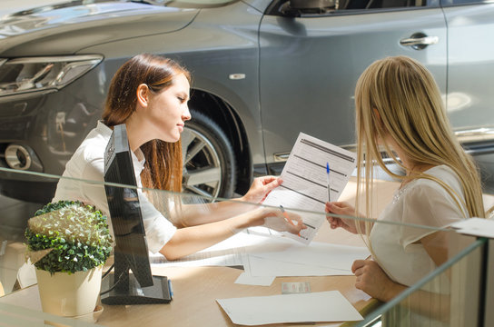 Девушки подписывают контракт на покупку нового автомобиля
