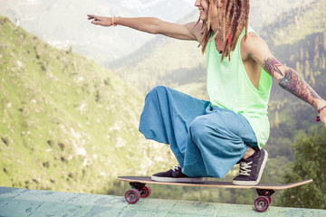 Hippie young and handsome man with longboard skateboard at mountain