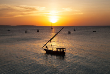 A boat in the sunset of the paradise island Zanzibar, a guy is relaxing in the bow of the boat.