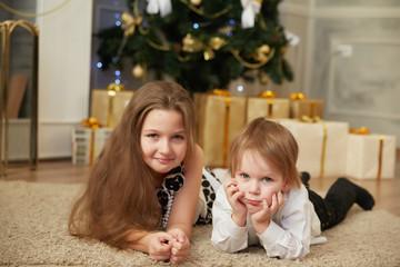 Cheerful girl and boy lying on the floor near a Christmas tree