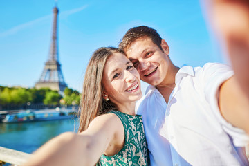 Young romantic couple making selfie near the Eiffel tower