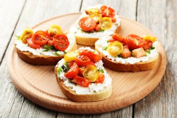 Tasty fresh bruschetta with tomatoes on cutting board on grey wo