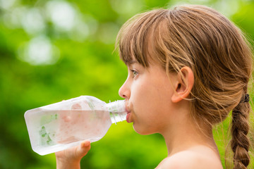 Child drinking clean tap water from transparent plastic bottle