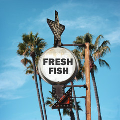 aged and worn vintage photo of fresh fish sign and palm trees
