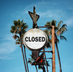 aged and worn vintage photo of closed sign and palm trees