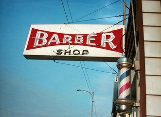 aged and worn vintage photo of neon barber shop sign