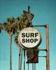 aged and worn vintage photo of surf shop sign with palm trees