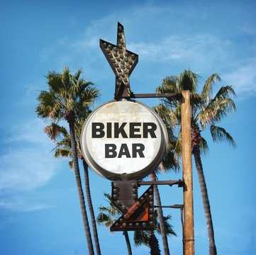 aged and worn vintage photo of biker bar sign with palm trees