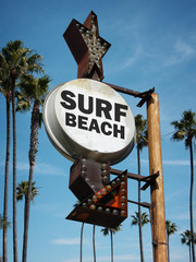 aged and worn vintage photo of surf beach sign and palm trees