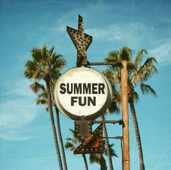 aged and worn vintage photo of summer fun sign with palm trees