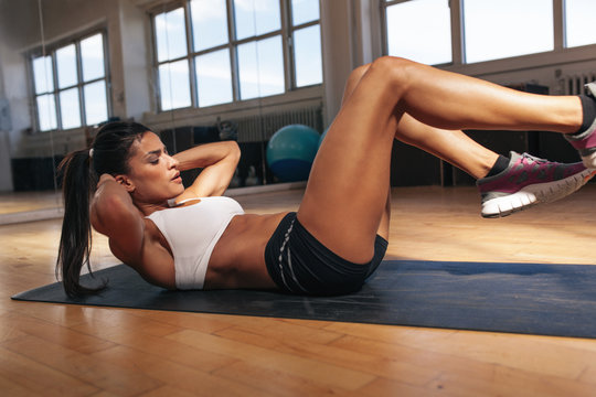 Muscular woman doing abs workout