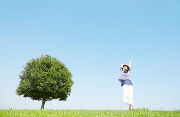Wall Mural - 一本木のある原っぱに立つ女性 背伸び