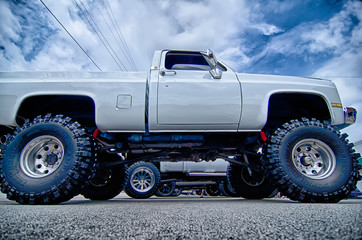 huge truck with huge wheels at a classic car show in a small tow