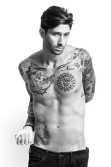 Sexy tattooed man portrait looking at camera black and white