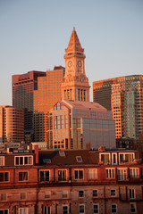 Commerce House Tower (built 1910) and Boston Skyline with condos below it at sunrise as photographed from Lewis Wharf, Boston, MA.