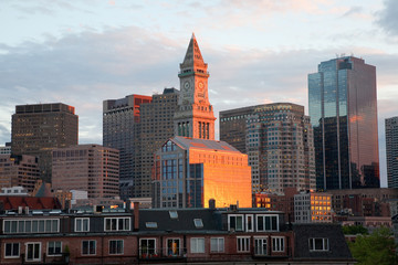 Sunset reflects in windows of Boston skyline and Commerce House Tower, Boston, MA.