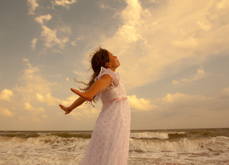 Beautiful girl on sunny beach.  Freedom and peace concept