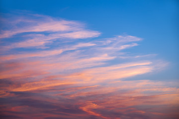 Pink and orange clouds in a blue sky at sunset