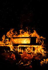 Lagerfeuer vor schwarzem Hintergrund bei Nacht