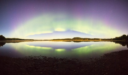 Northern lights with reflections on the lake at night