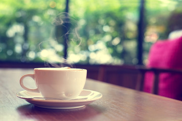 Cup of coffee on table in cafe Morning light , vintage or retro color toned