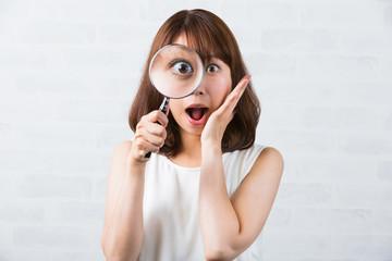 虫眼鏡を使う女性