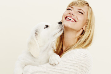Laughing young woman with pet puppy, studio
