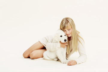 Blond lady embracing Labrador puppy in studio