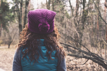 Curly hair woman in knitted hat in autumn forest