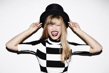 Excited young blond woman in top hat, portrait