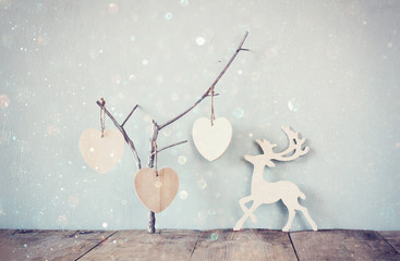 hanging wooden hearts over and wooden rain deer decoration over wooden background