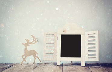 abstract filtered photo of decorative chalkboard frame and wooden deer over wooden table