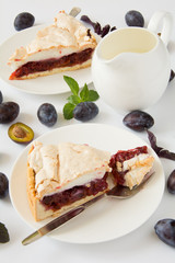 Homemade cake with plums on white background