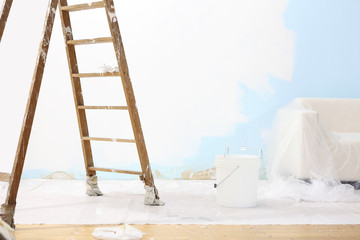 painter house concept, wooden ladder, bucket, and white wall