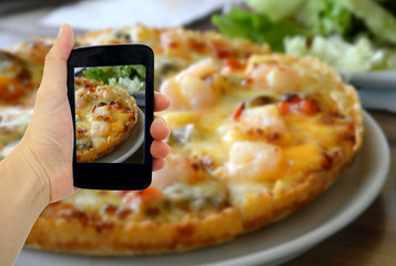 Woman hand taking a photo of Pizza with smartphone