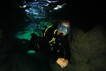 Scuba diver blonde woman cave diving