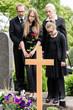 Familie steht in Trauer an Grab auf Friedhof bei Beerdigung