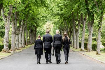 Familie läuft auf Allee im Friedhof in Trauer mit Blumen in der Hand