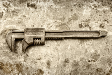 Vintage rusty adjustable spanner on an old iron background