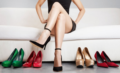 Wall Mural - Beautiful legs woman crossing legs on the sofa with many shoes. heels. Leg bodycare. Shopping.