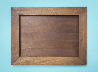 Old wooden picture frame on blue background
