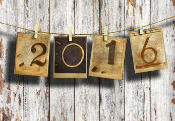 New year 2016 in old photo hanging on clothesline on wood background.