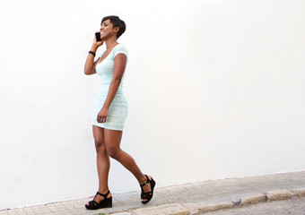 Attractive young woman walking on street with cell phone
