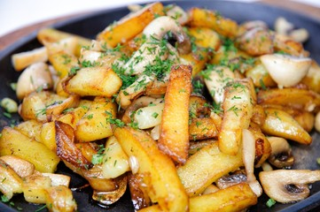 Fried potatoes with mushrooms in a skillet.
