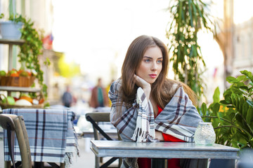 Portrait of a beautiful young girl sitting in a cafe on the stre
