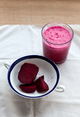 The beetroot smoothie with pieces of beetroot in the ceramic bowl