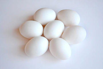 Seven white hen eggs on a white background