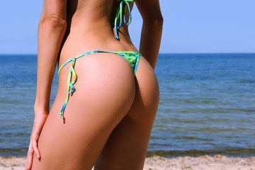 Sexy buttocks with drops of water of a young beautiful sporty woman in bikini posing on the beach